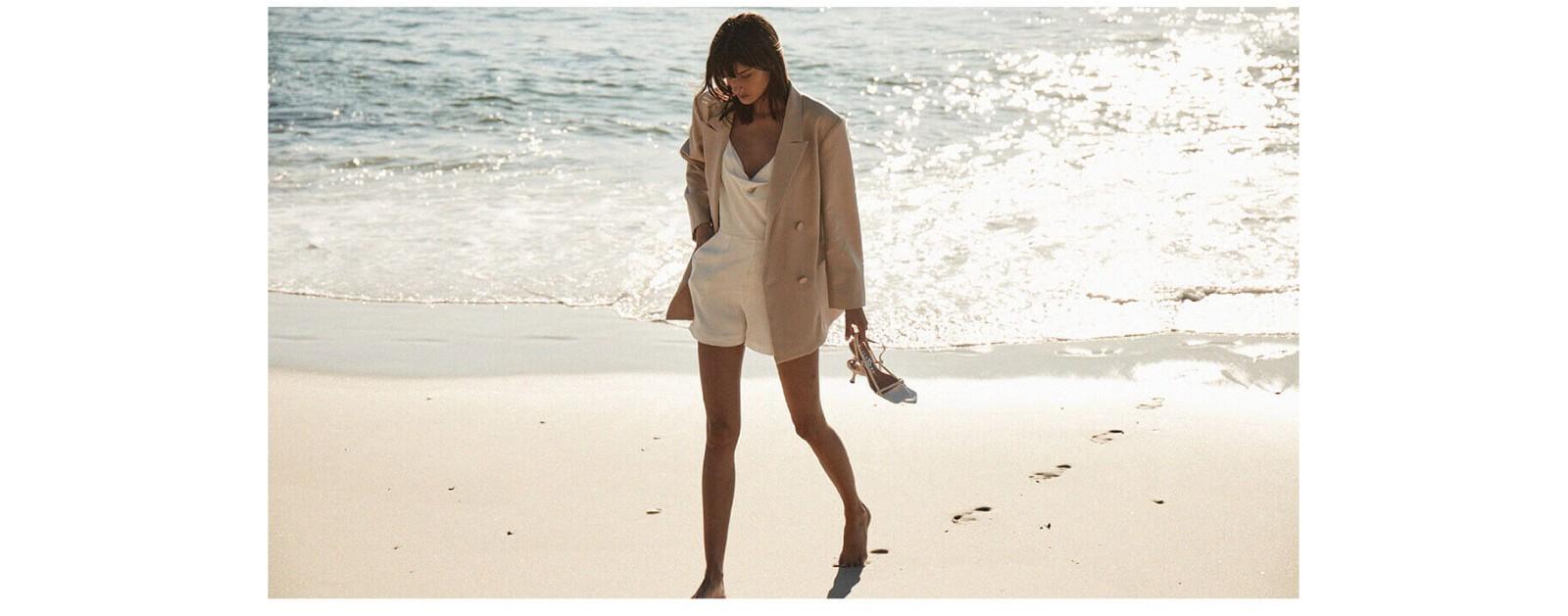 Bardot woman walking on beach in beige romper and blazer carrying shoes